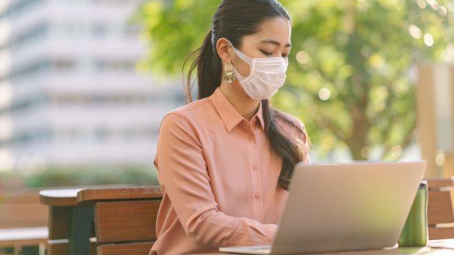 Young businesswoman wearing face mask in city