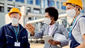 Black female architect and civil engineers with protective face masks talking at construction site