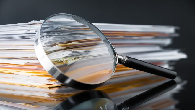 Magnifying glass with stack of papers