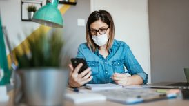 Woman wearing mask while looking at her phone