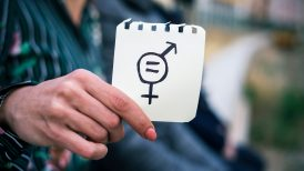 Woman holding paper with gender equality symbol written on it
