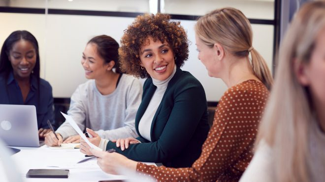 Group of women collaborating in meeting around table