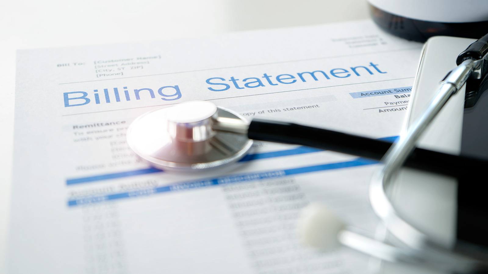 Stethoscope laying on billing statement
