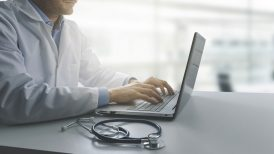 Doctor looking on laptop at a healthcare portal