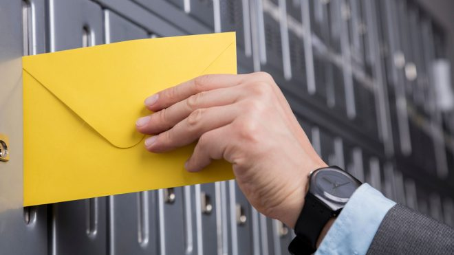 Person putting envelope in mailbox