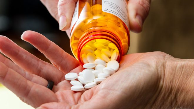 Person taking multiple pills out of pill bottle
