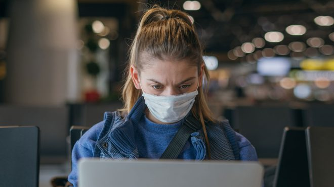 Woman wearing face mask and working on laptop