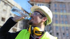 Worker at construction site with bottle of water