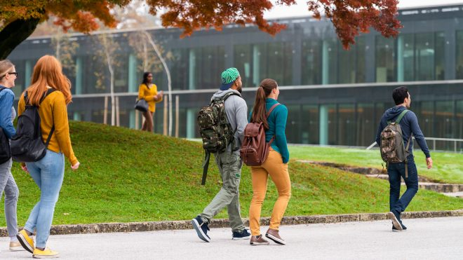 Group of students walking and standing in front of a modern glass university building