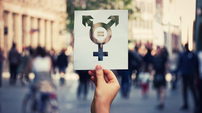Person holding up paper with transgender icon