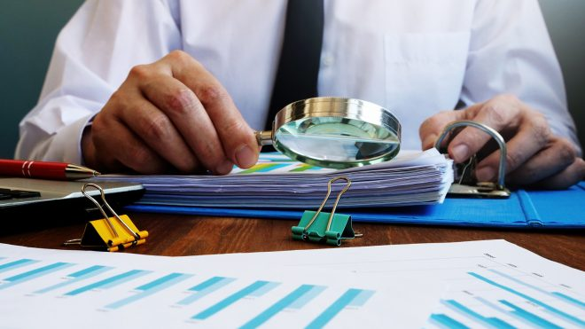 Business person checking report with magnifying glass