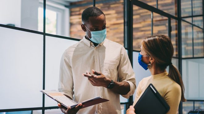 Business people wearing protective face masks at work during COVID-19 pandemic