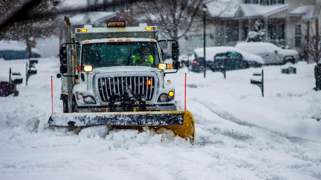Snow plow on a city street during winter storm