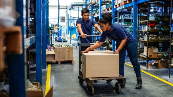 Distribution warehouse workers moving boxes in plant