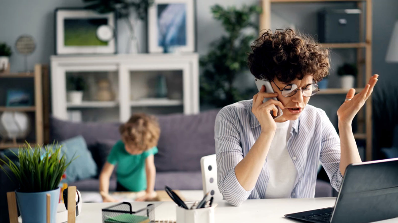 Mother working at home with child in background